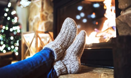 Cozy feet in socks by fire