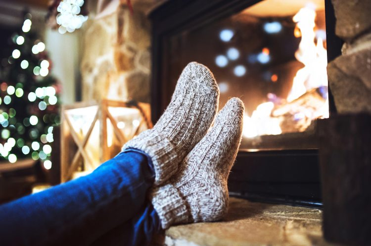 Cozy feet in socks by fire