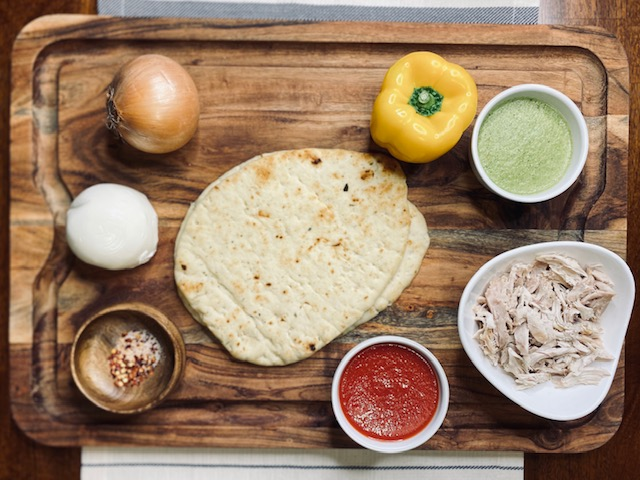 Ingredients for chicken salsa verde naan on a wood board