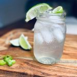 Cocktail in mason jar with limes