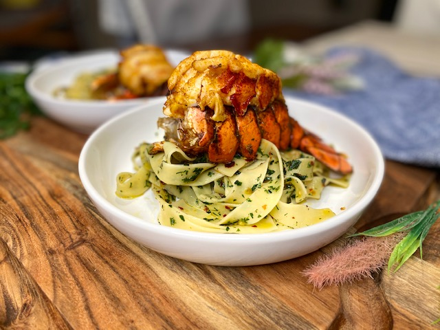 Lobster over pasta in bowl