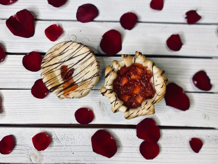 Strawberry tarts on white wood with rose petals