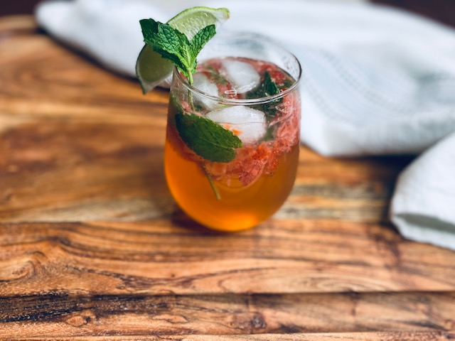 Strawberry mojito with mint and lime on wooden board