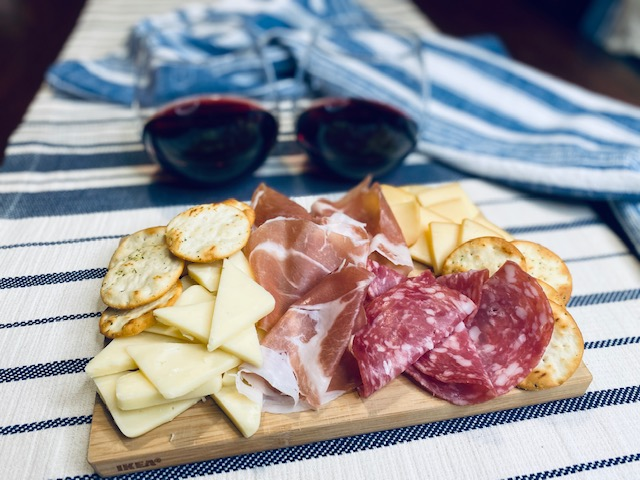 Two wine glasses filled with cheese and meat board