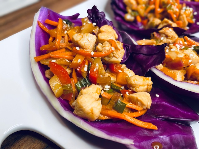 Red cabbage with chicken and veggies in it with toasted sesame seeds on top