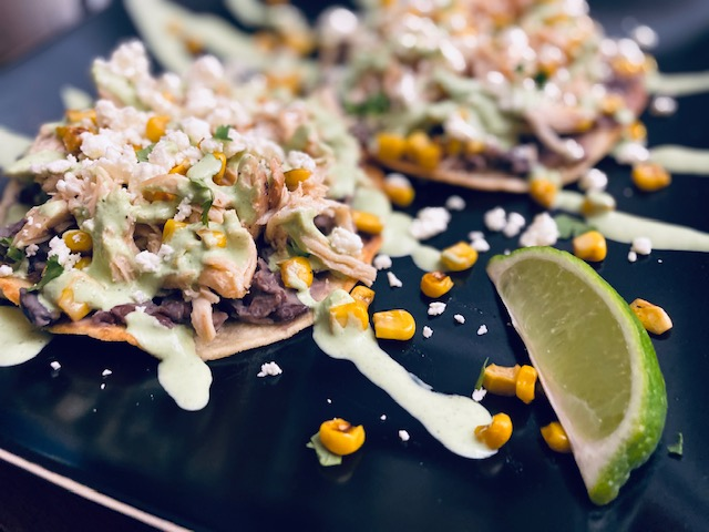 Tostadas with many toppings on a black plate with a lime wedge