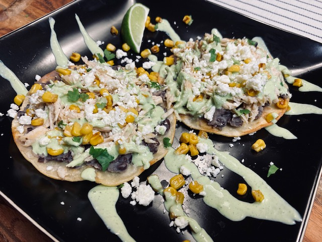Tostadas on a black plate with cilantro lime sauce