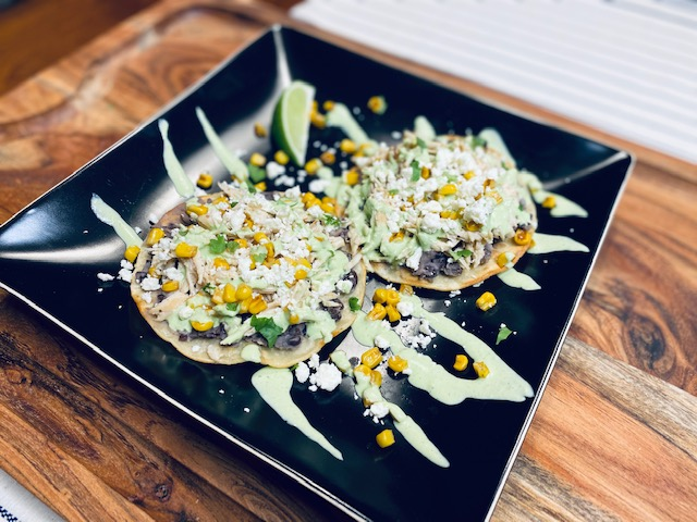 Two tostadas on a black plate