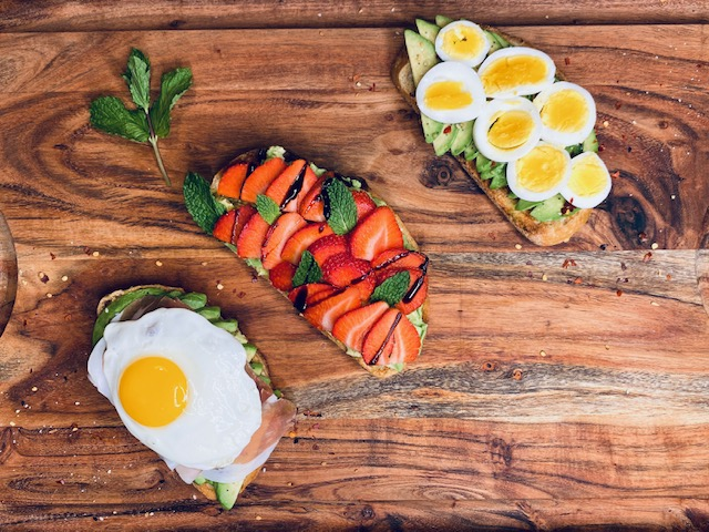 Avocado toast 3 ways on a wooden board