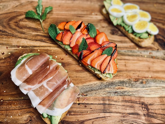 Avocado toast with different toppings on a wooden board