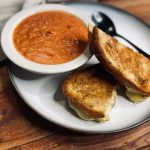 Tomato soup with grilled cheese on white plate