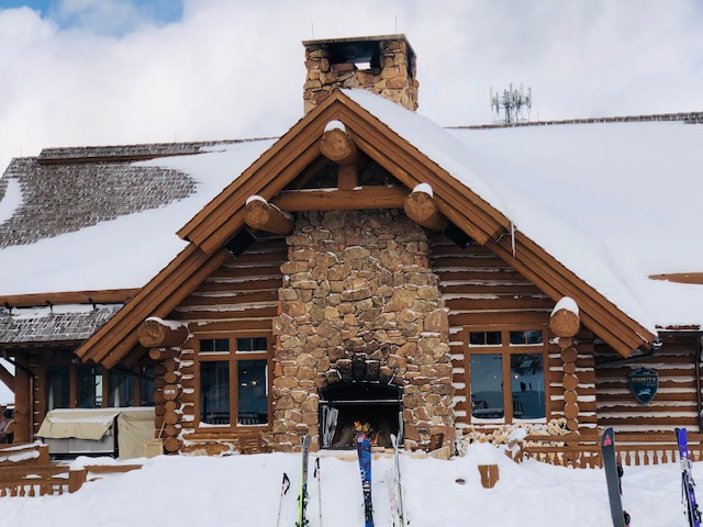 Snowy cabin with skis in front