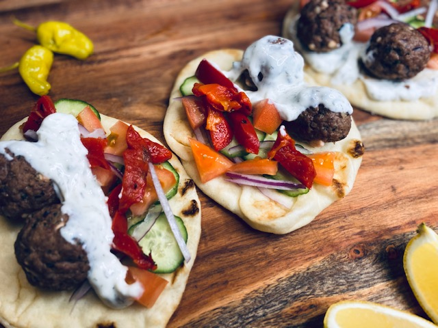 Naan with greek meatballs and toppings on a wooden board