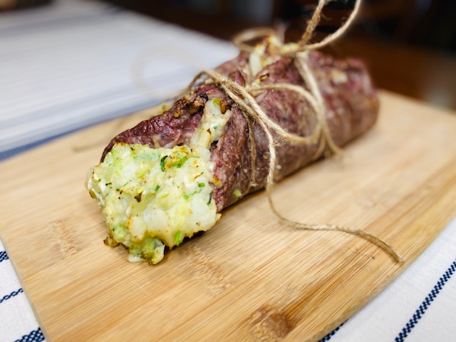 Steak on a cutting board stuffed with potatoes