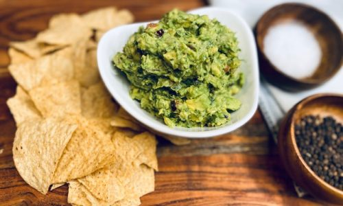 Guacamole with chips on a wooden board