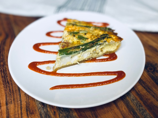 Quiche on a white plate with sauce