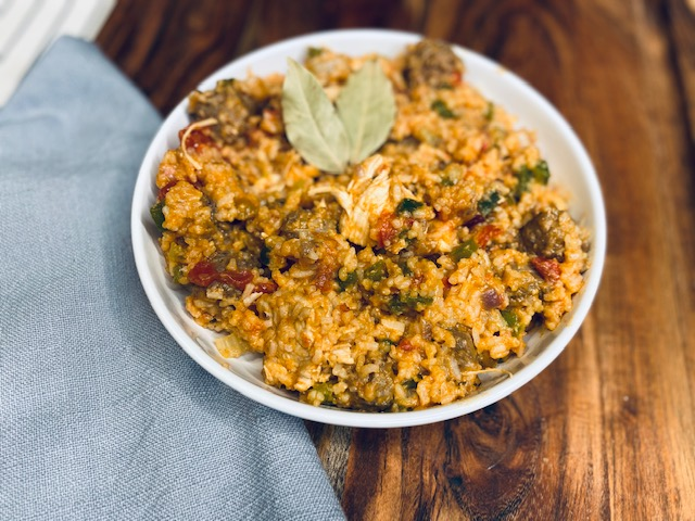 Jambalaya in a white bowl on a wooden board with a gray cloth