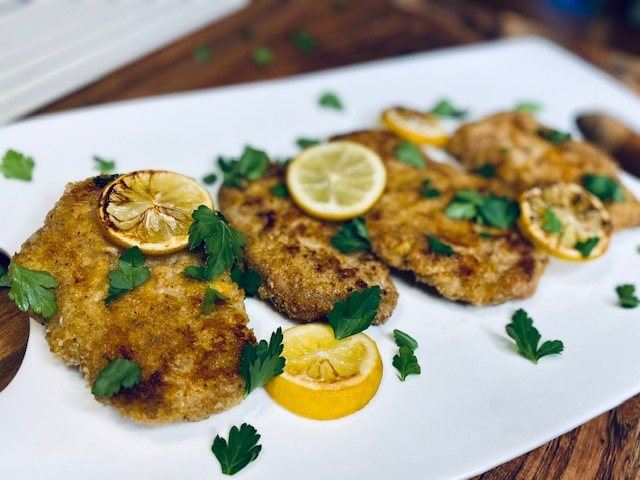 Pork schnitzel with parsley and lemon on a white plate