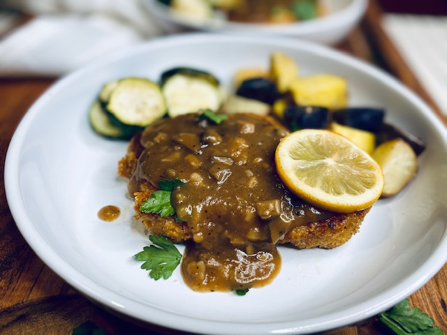Pork schnitzel with lemon on a white plate