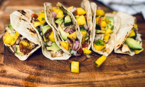 Fish tacos with mango salsa on a wooden board