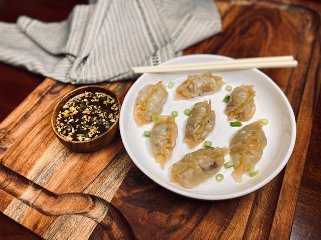 Pork dumplings and sauce on a wooden board
