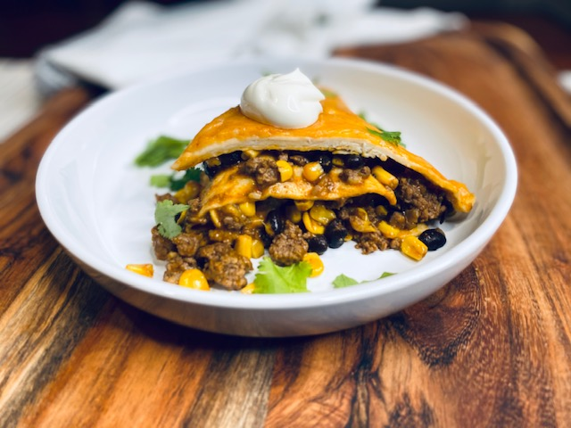 Enchilada lasagna with sour cream on a plate