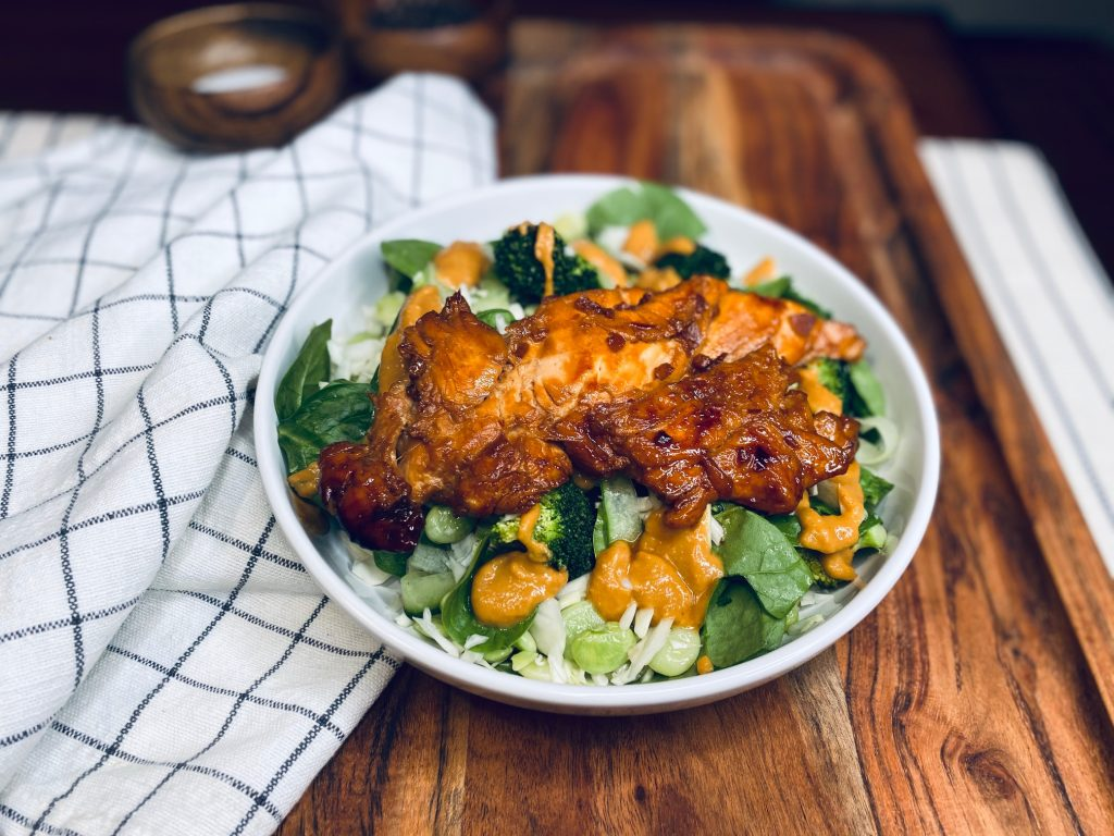 Chicken over greens on a wooden board