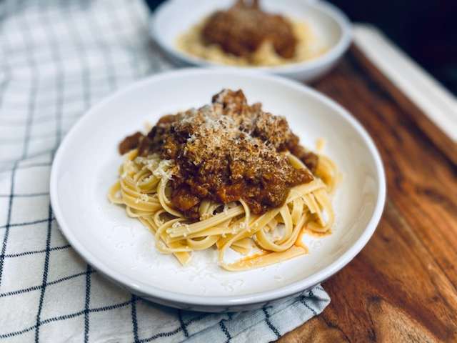 Pasta with chorizo tomato sauce on a white plate