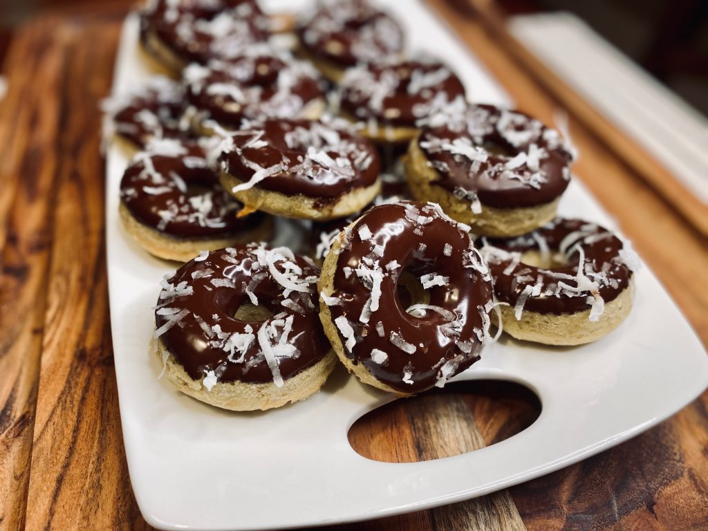 Chocolate covered donuts with coconut shavings