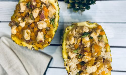 Pineapple bowls with chicken and rice on a white board