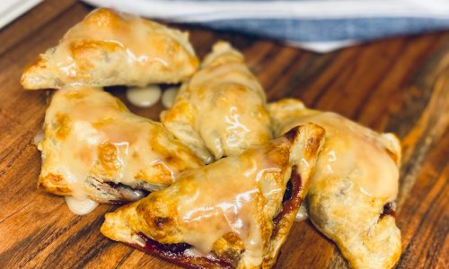 Lemon glazed blackberry turnovers on a board