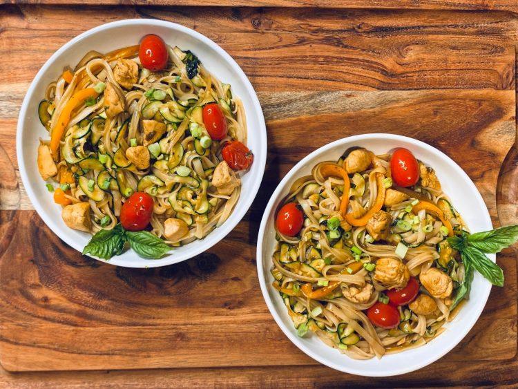 Two bowls of Drunken Noodles on a wooden board
