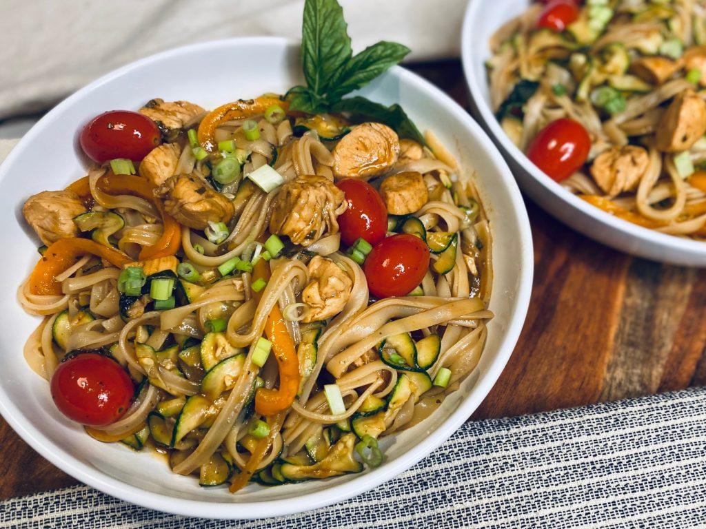 A bowl of Drunken Noodles with basil