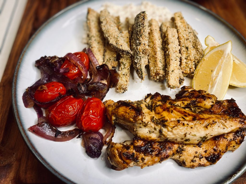 Mediterranean chicken with eggplant fries on a white plate