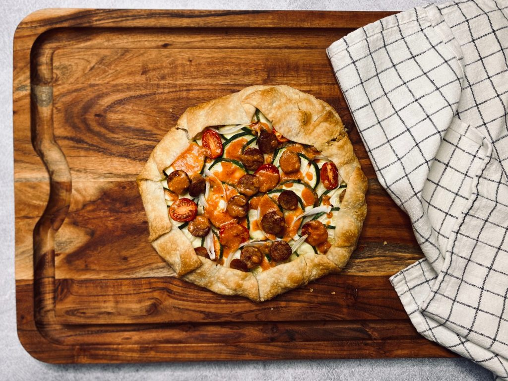 Galette with sausage and veggies on a wooden board