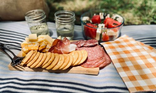 Picnic blanket with cheese board, watermelon, and wine