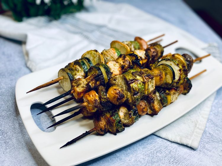 Skewers with salmon and pesto on a white plate