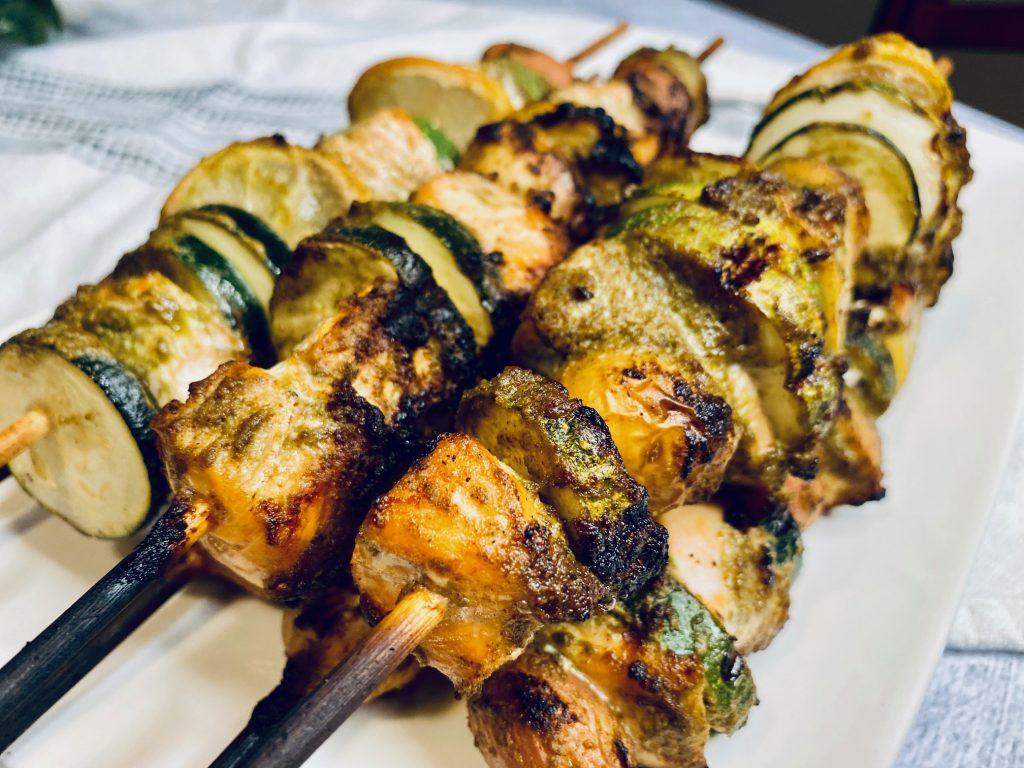 Salmon, zucchini, and lemons on skewers with pesto