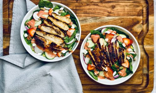 Two white bowls filled with spinach and strawberry salad