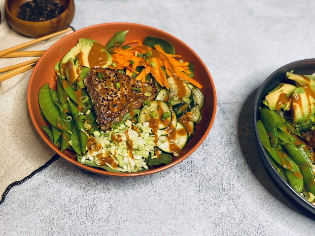 Two seared tuna bowls loaded with veggies