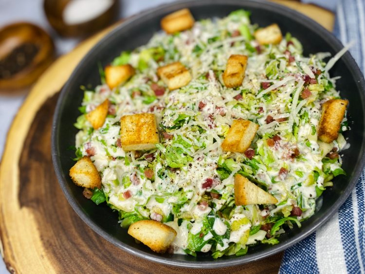Gray bowl with Brussel sprouts and dressing