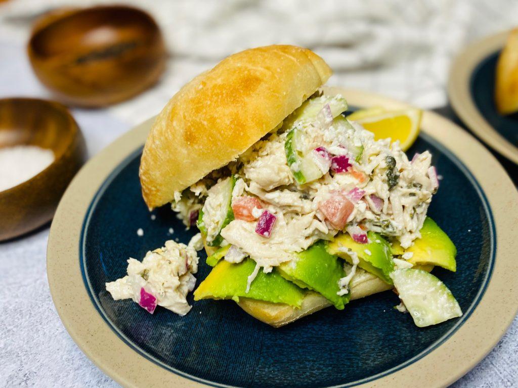 Blue plate with a greek chicken salad sandwich