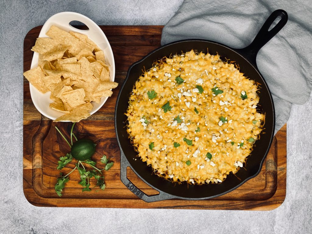Wooden board with mexican street corn dip in cast iron skillet