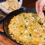 Mexican street corn dip getting scooped with a chip