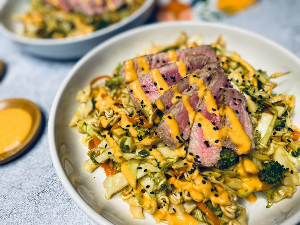 Tuna with cabbage and ramen noodles in white bowl