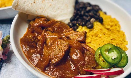 Chili colorado with yellow rice and a tortilla
