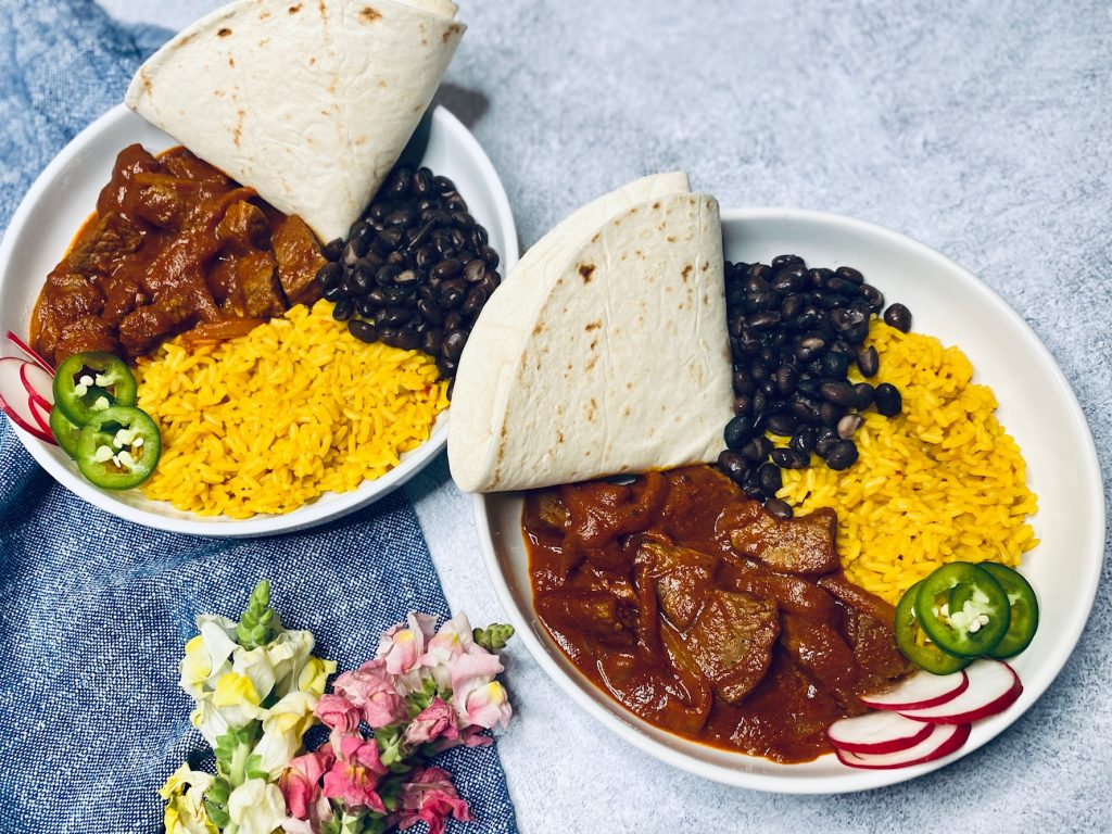 Chili Colorado with rice, beans, and tortillas