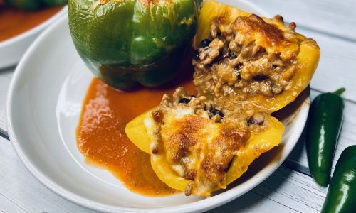 Enchilada stuffed peppers cut open on a white plate