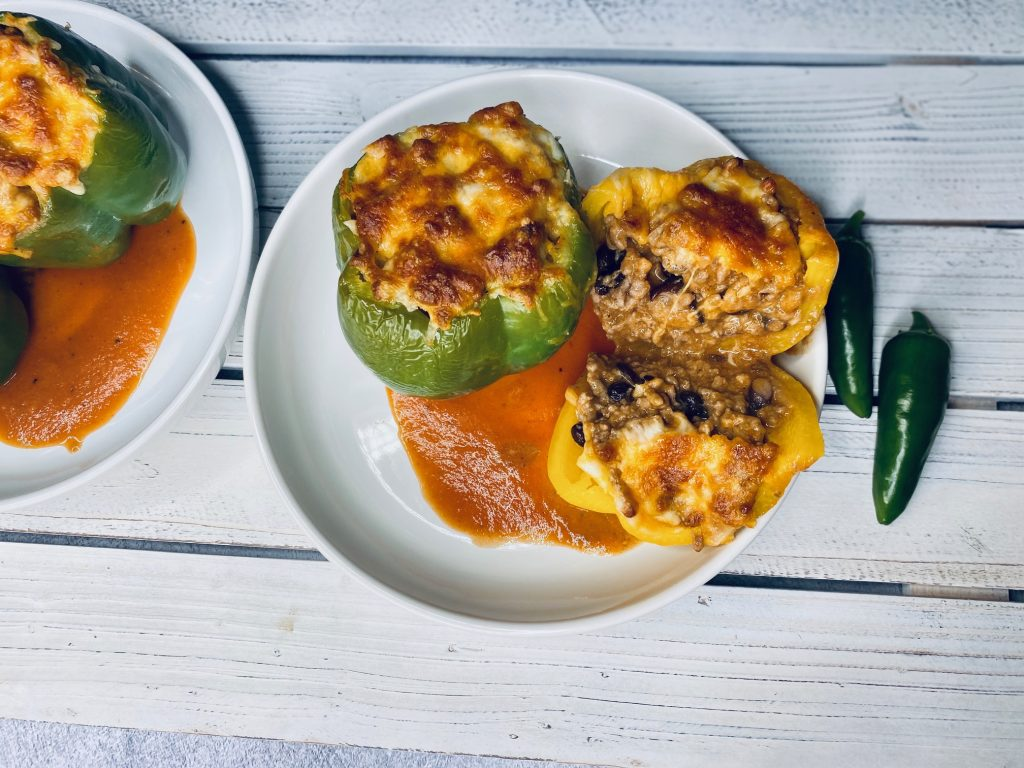 White wooden board with enchilada stuffed peppers