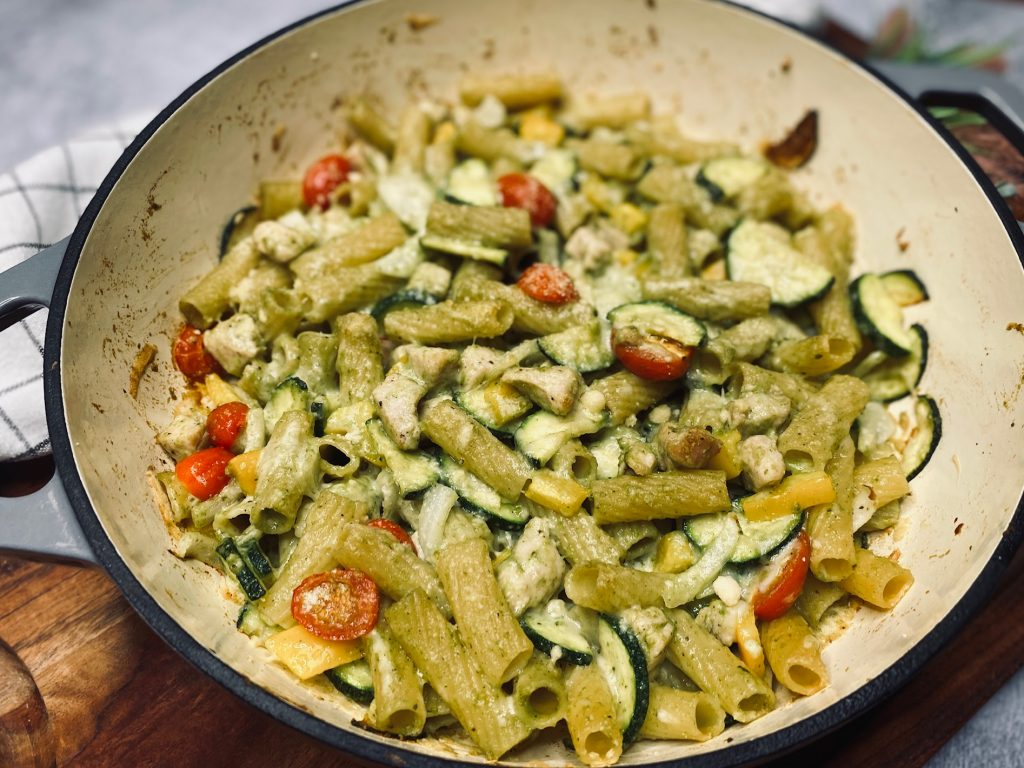 Dutch oven filled with baked pasta in pea basil pesto sauce